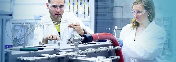 Two researchers (male and female) working at set-up of the LOHC-dehydrogenation unit (Image: EAM/Minx)